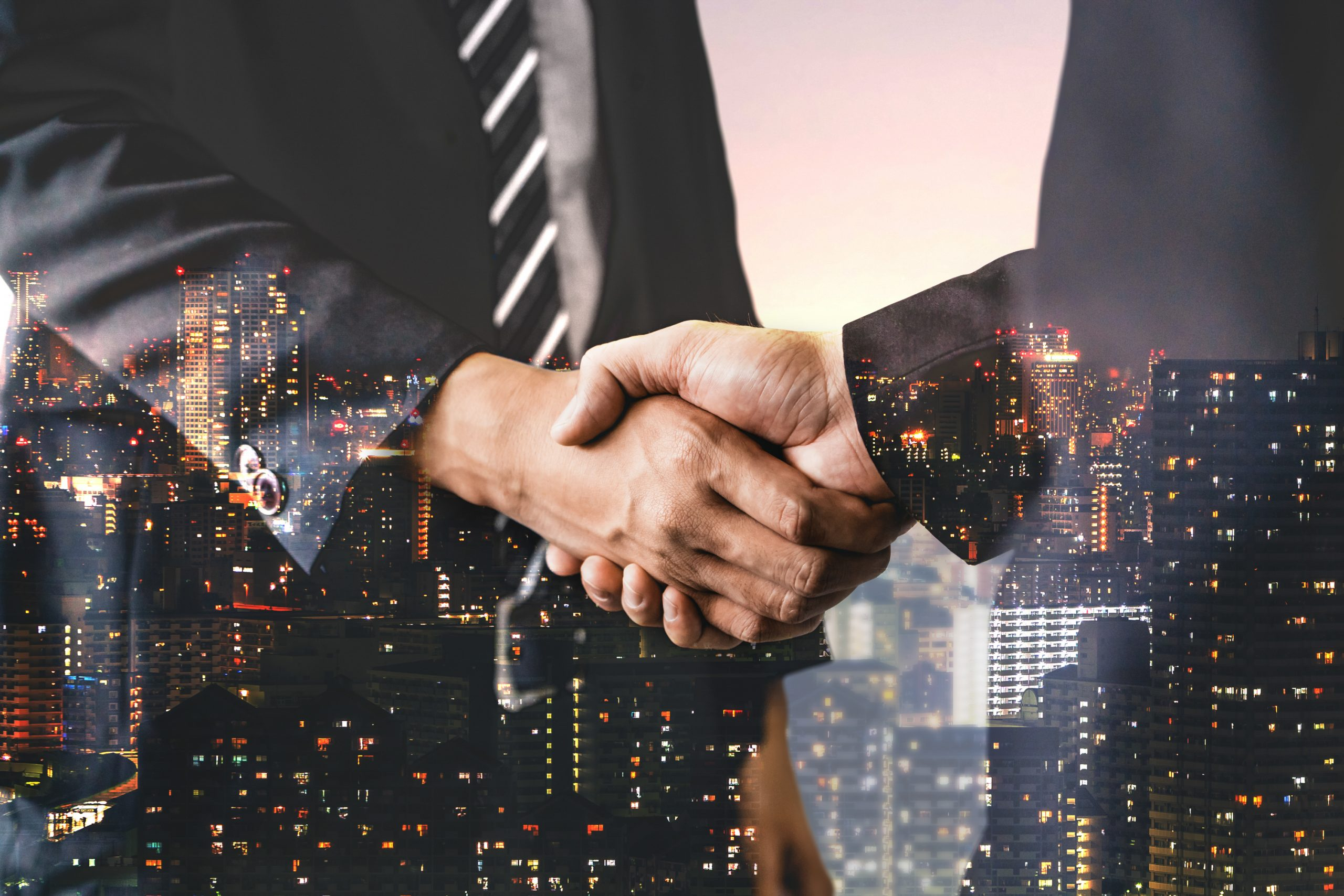 Double exposure image of business people handshake on city office building in background showing partnership success of business deal. Concept of corporate teamwork, trust partner and work agreement.